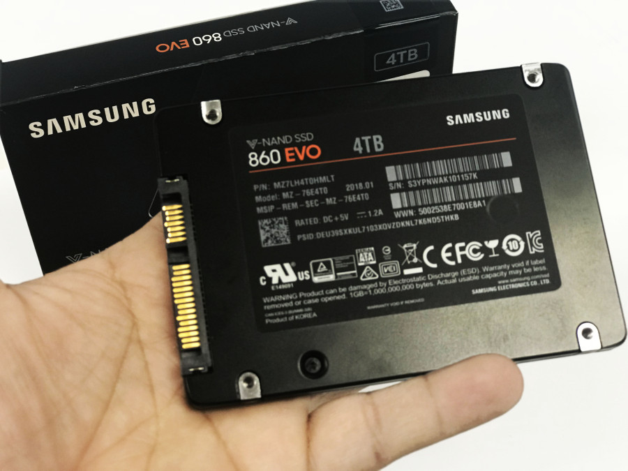Samsung V-Nand SSD 860 EVO 4TB on a technicians hand with the case on the background