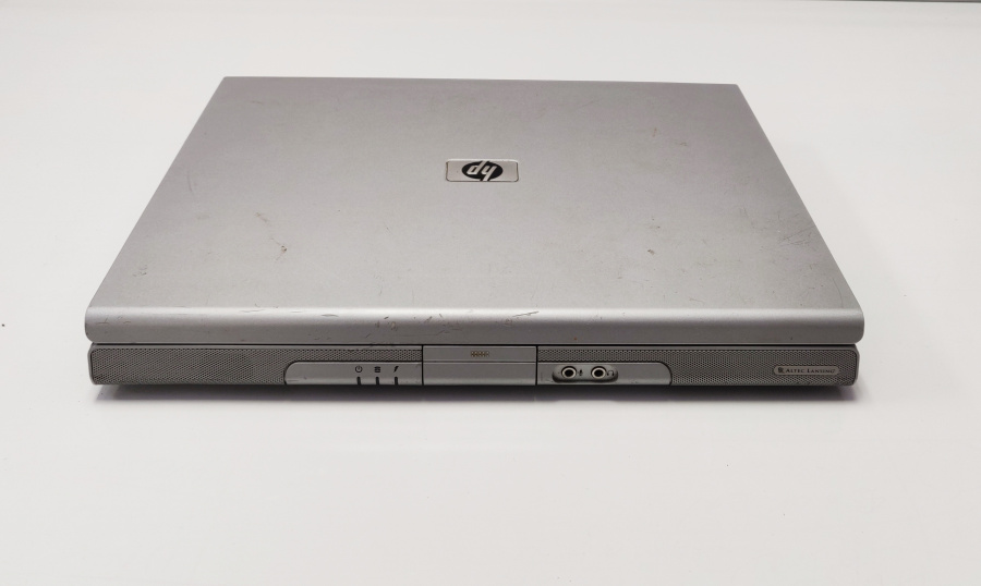 Old HP laptop computer with two 3.5mm headset jack ports and three lights on the front.