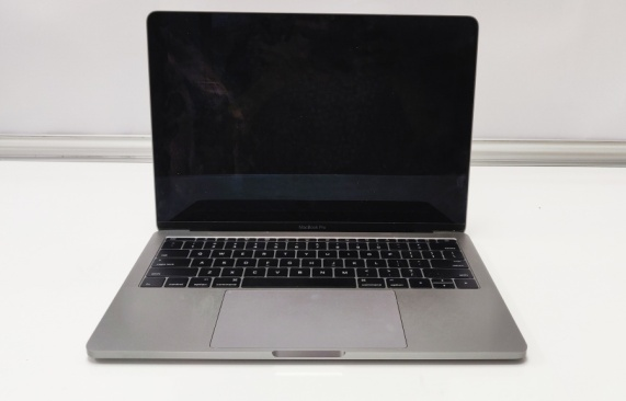 Macbook Pro on a white background with lid open at 90 degree and black screen with no display.