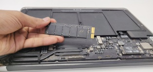PCie SSD installation in an old Macbook laid on the back with motherboard exposed by PCServiceDallas Technician holding the PCie SSD card